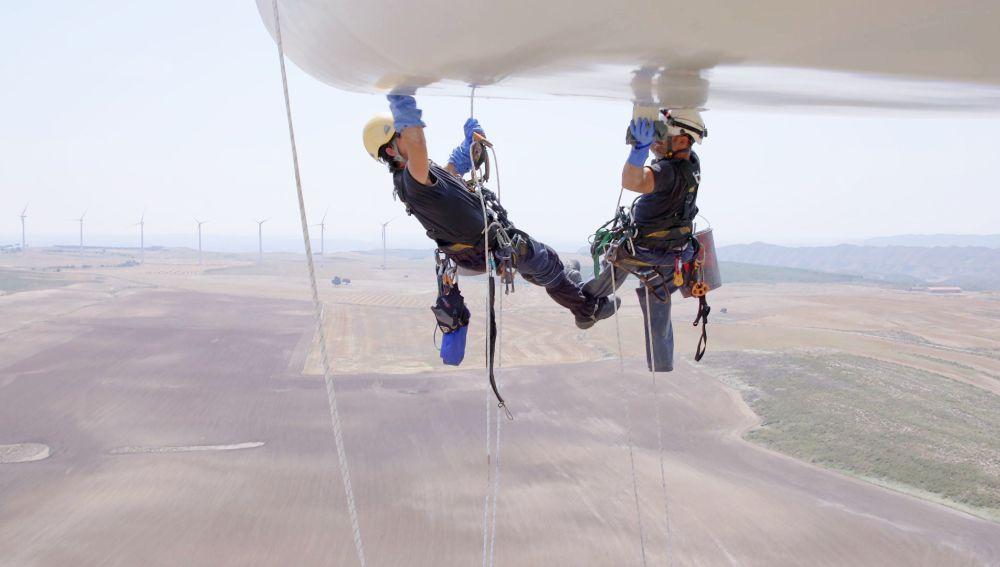 Colgados a 80 metros de altura para limpiar un molino de viento